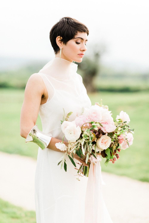 Mariée aux cheveux courts tenant un bouquet de fleurs