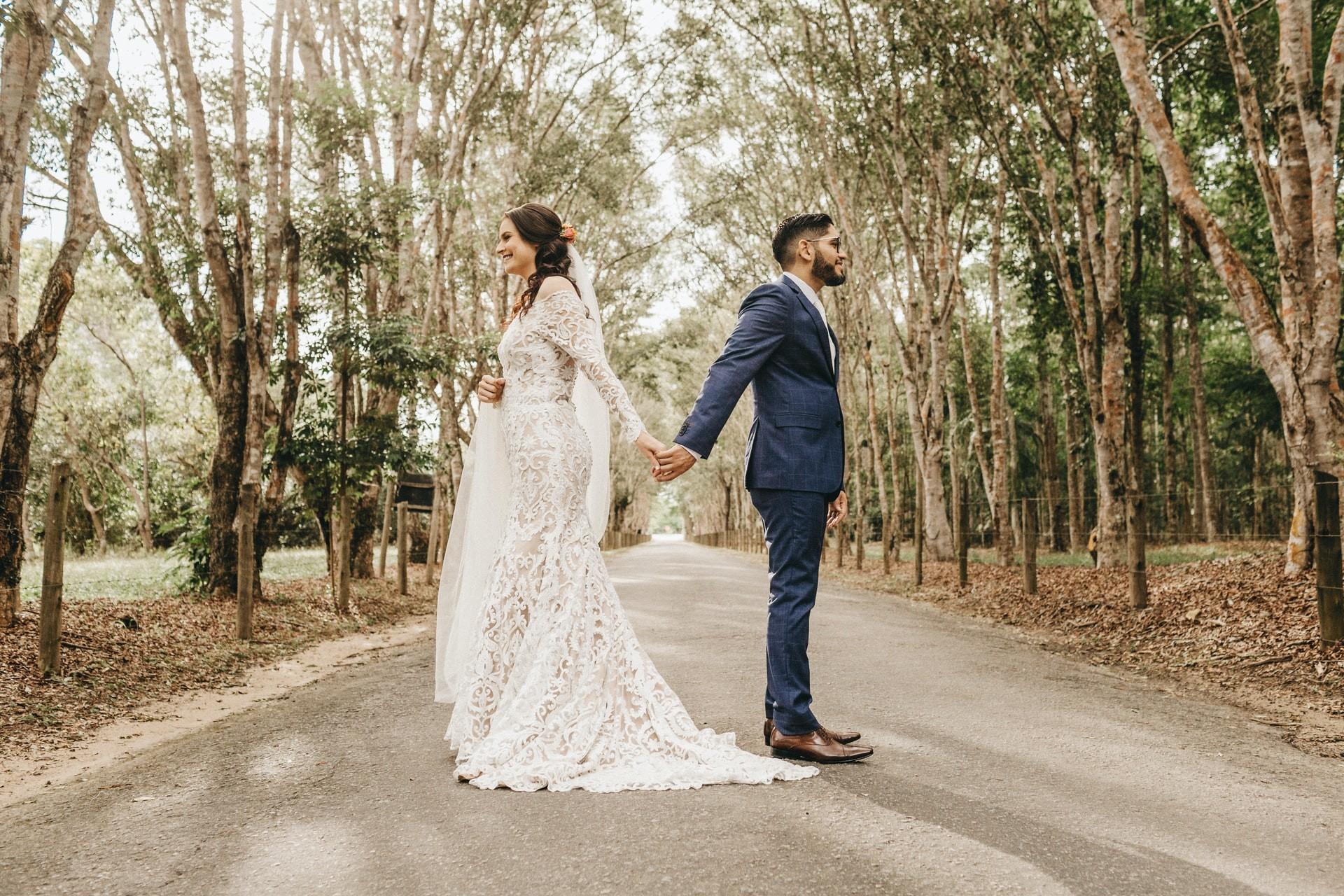 Mariée et le marié debout dos à dos pour la photo
