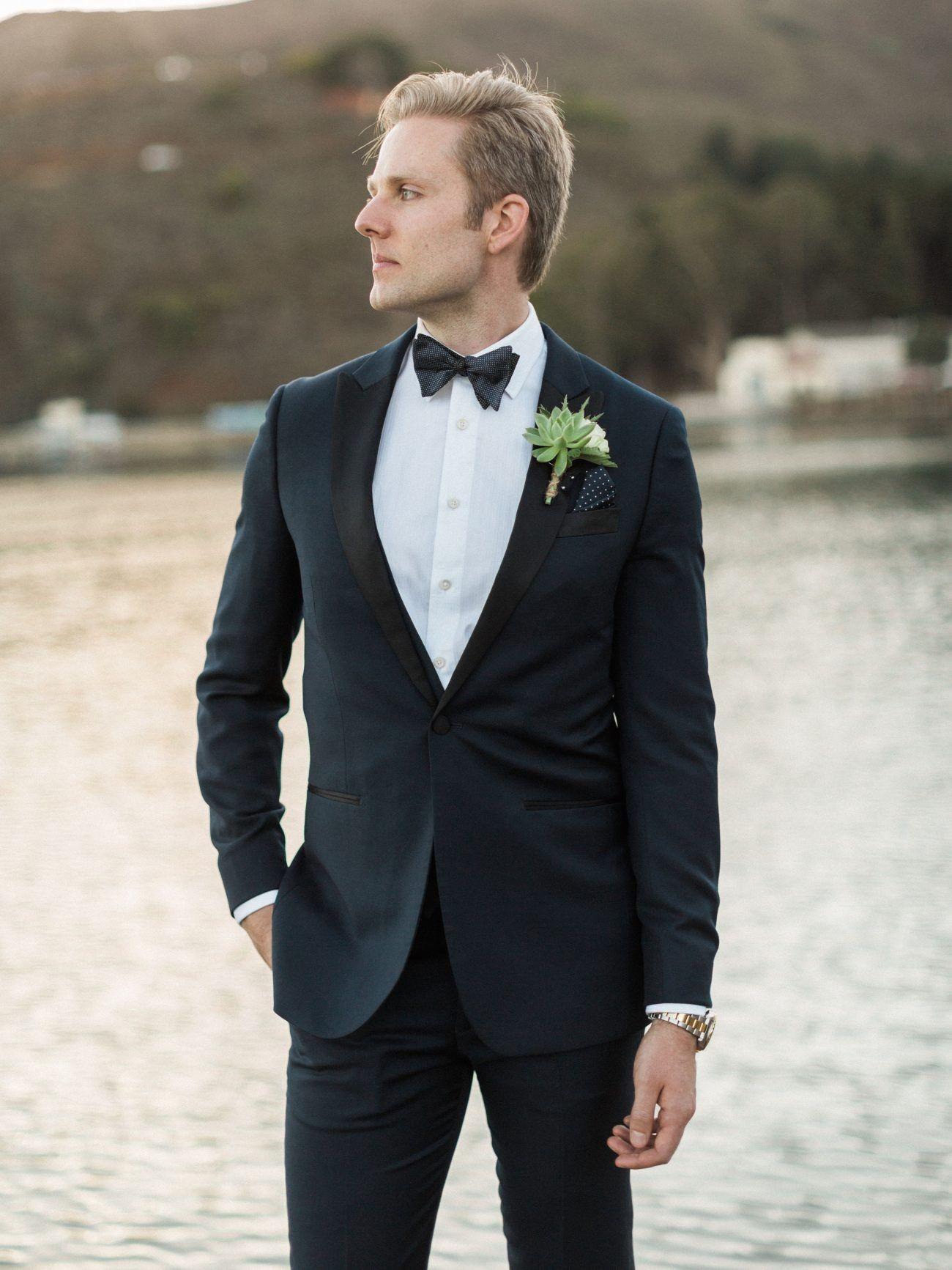 Marié portant un costume et posant devant un lac