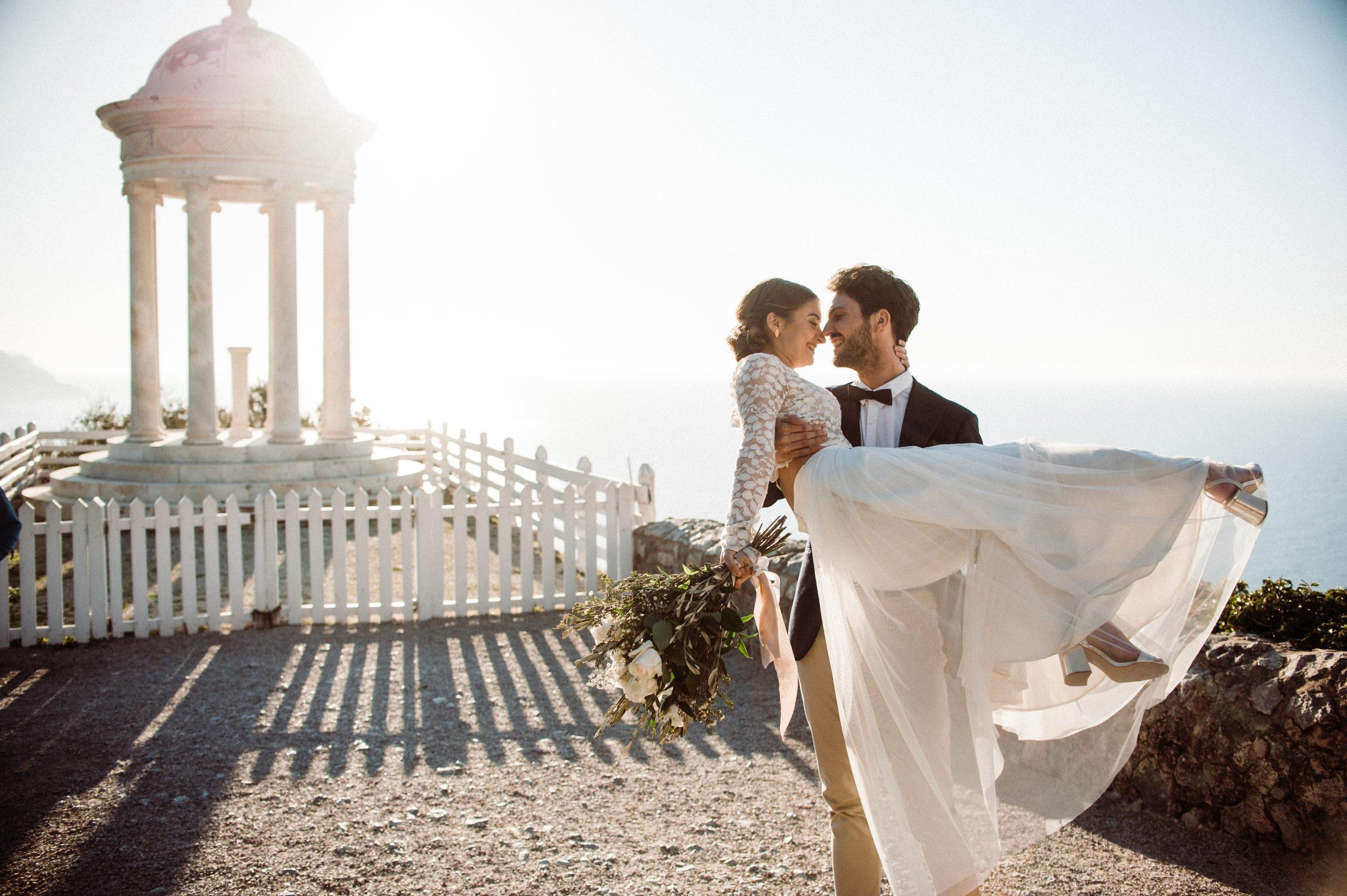 Groom holding bride en mariage à destination romantique sur une île espagnole
