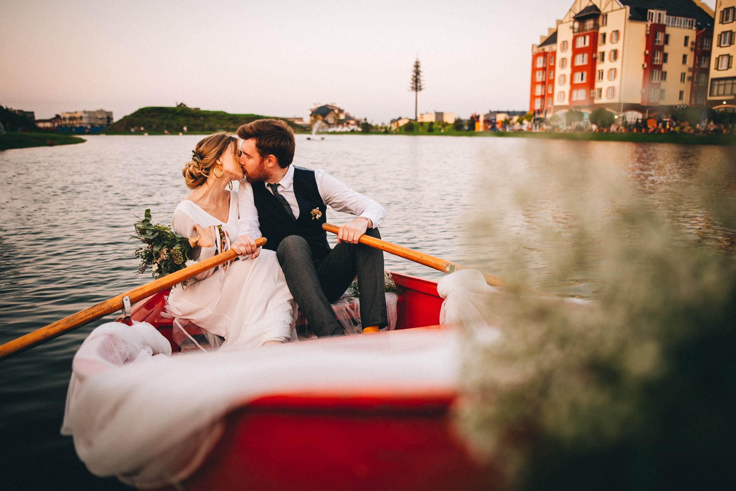 Mariée et marié s'embrasser sur une barque